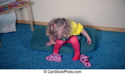 Nervous girl playing with her shoes. Child cant put sandal on