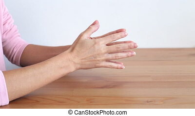Nervous girls's hands on a wooden table