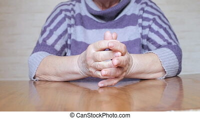 Nervous hand movements of a senior woman