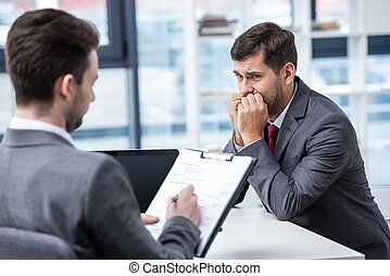 Nervous man in formal wear looking at businessman writing on...