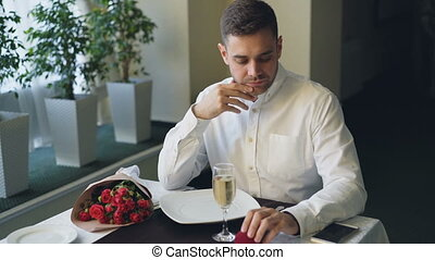 Nervous man is sitting alone at table in restaurant,...