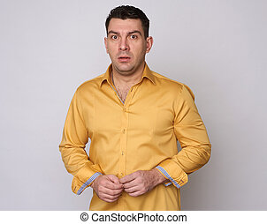 nervous man on grey - nervous man in yellow shirt looking at...