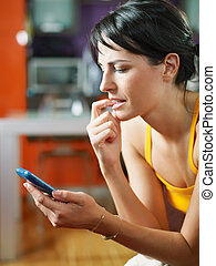 mid adult woman staring at her mobile phone and biting nails. Vertical shape, waist up, side view, copy space