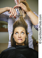 nervous woman in hairdresser shop cutting long hair
