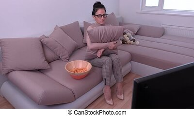 Nervous woman watching TV