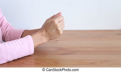 Nervous woman's hands on a wooden table