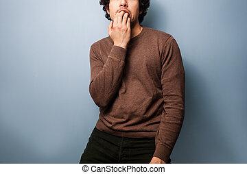 Nervous young man biting his nails