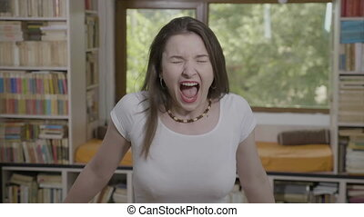 Nervous young woman screaming at home expressing angry...