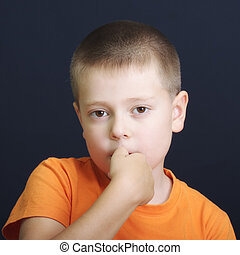 Nervously biting fingernails - Boy in orange shirt nervously...