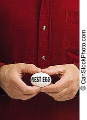 NEST EGG written on egg held by man