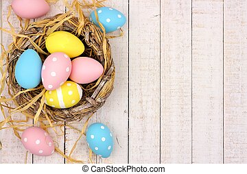 Nest side border with pink, yellow & blue Easter Eggs against white wood