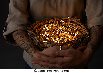 Nest with Christmas lights in the woman hands on black background
