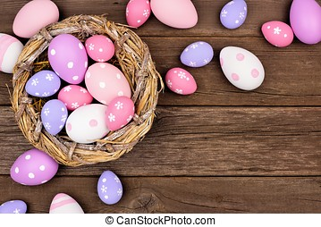 Nest with pink, purple and white Easter Eggs against wood
