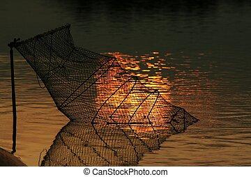net fishing on the background of the setting sun illuminated water 2