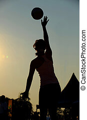 A netballer is sillouetted as she jumps for the ball.