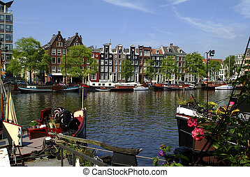 Netherlands, Amsterdam, Amstel river with boats and homes ...