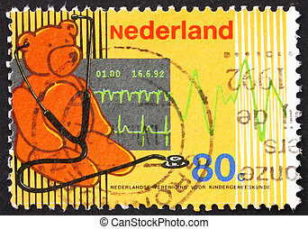 NETHERLANDS - CIRCA 1992: a stamp printed in the Netherlands shows Teddy Bear and Stethoscope, Cardiogram, Centenary of Netherlands Pediatrics Society, circa 1992