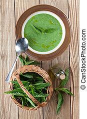 Nettle cream soup on wooden background. Shallow dof