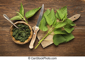 Nettle fresh green leaves on a wooden background.