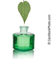 Nettle leaf extract, drop falling into a green bottle.