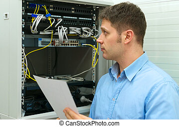 Network administrator with manual in server room.