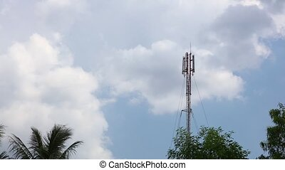 Network communication tower mast cloudscape and treetops -...