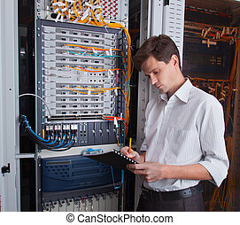 Network engineer in server room with pen and tablet