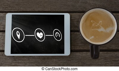Network of connection icons on digital tablet screen and coffee cup on wooden surface
