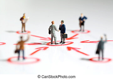 Two tiny miniature businessmen shake hands in the centre of a networking web surrounded by linked colleagues offering support and teamwork in business