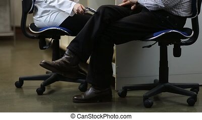 Neurologist testing knee reflex of male patient - Female...