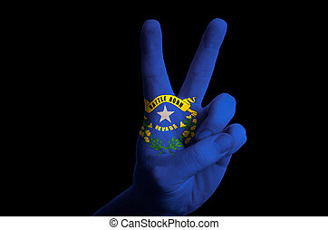 Hand with two finger up gesture in colored nevada state flag as symbol of winning, victorious, excellent, - for tourism and touristic advertising, positive political, cultural, social management of country