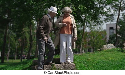 Elderly family going downstairs outdoors supporting each other