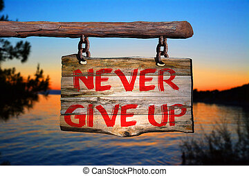 Never give up motivational phrase sign on old wood with ...