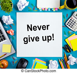 Never give up. Office table desk with supplies, white blank note pad, cup, pen, pc, crumpled paper, flower on blue background. Top view