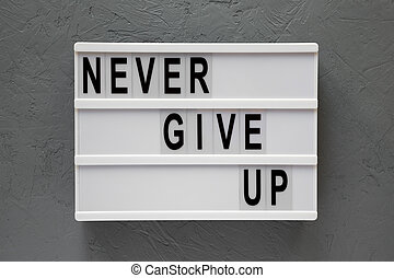 'Never give up' words on modern board over concrete background. Flat lay, from above, overhead. Closeup.