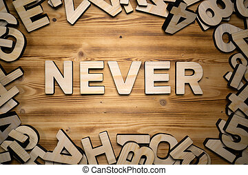 NEVER word made with block letters lying on wooden board