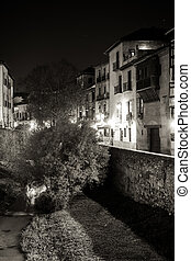 Urban scene of a river crossing the old part of the city of Granada, Spain, taken at night