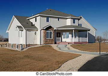 new american home - brand new house on the outskirts of town against a blue sky