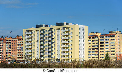 new apartment houses on background of blue sky