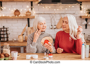 Two good-looking elderly women trying new cream