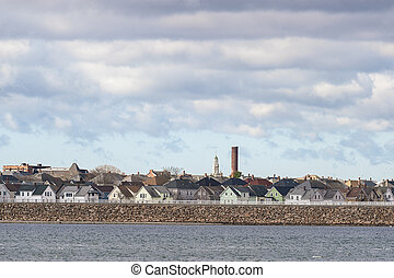 Smokestack and church steeple stand out over New Bedford neighborhood behind hurricane protection barrier
