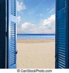 new beginings concept - open blue door to sandy beach and...