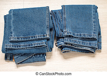 New blue jeans on wooden background.