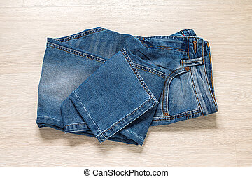 New blue jeans on wooden background