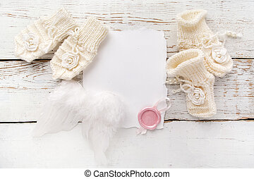 New Born or baptism Greeting Card. Blank with baby girl shoes, gloves and angel wingson white wooden background