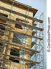 New Building Construction with Scaffolding Closeup. Vertical Photo. Residential Building Development.