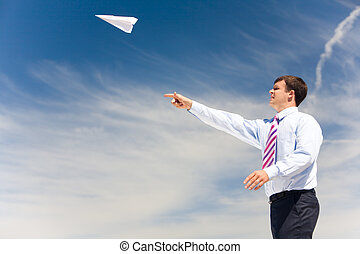 New business - Image of businessman letting paper airplane...
