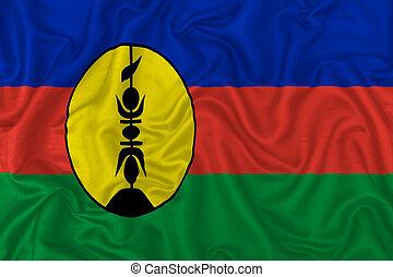 New Caledonia flag on wavy silk textile fabric background.