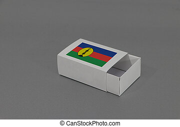 New Caledonia flag on white box on grey background, paper packaging for put match or products.