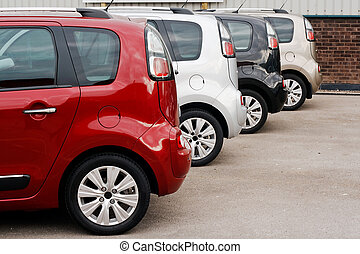 row of new cars for retail sale in a motor dealer yard showing same model in different color choices